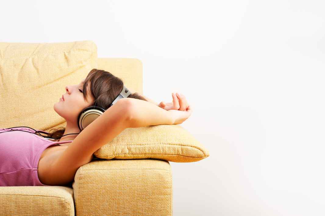 Woman-lying-on-a-cream-sofa-with-headphones-on--000004755895_Large.jpg