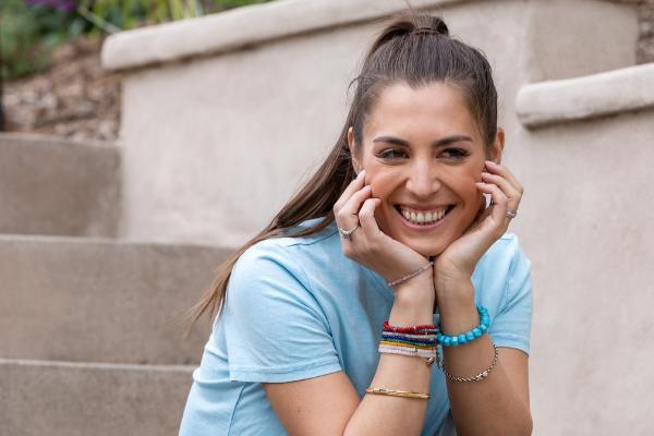 Alexandra Harbushka blue t-shirt sitting on stairs.png