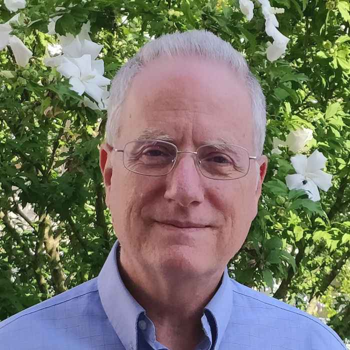 Head shot of David B. Alexander, in front of a blossoming tree