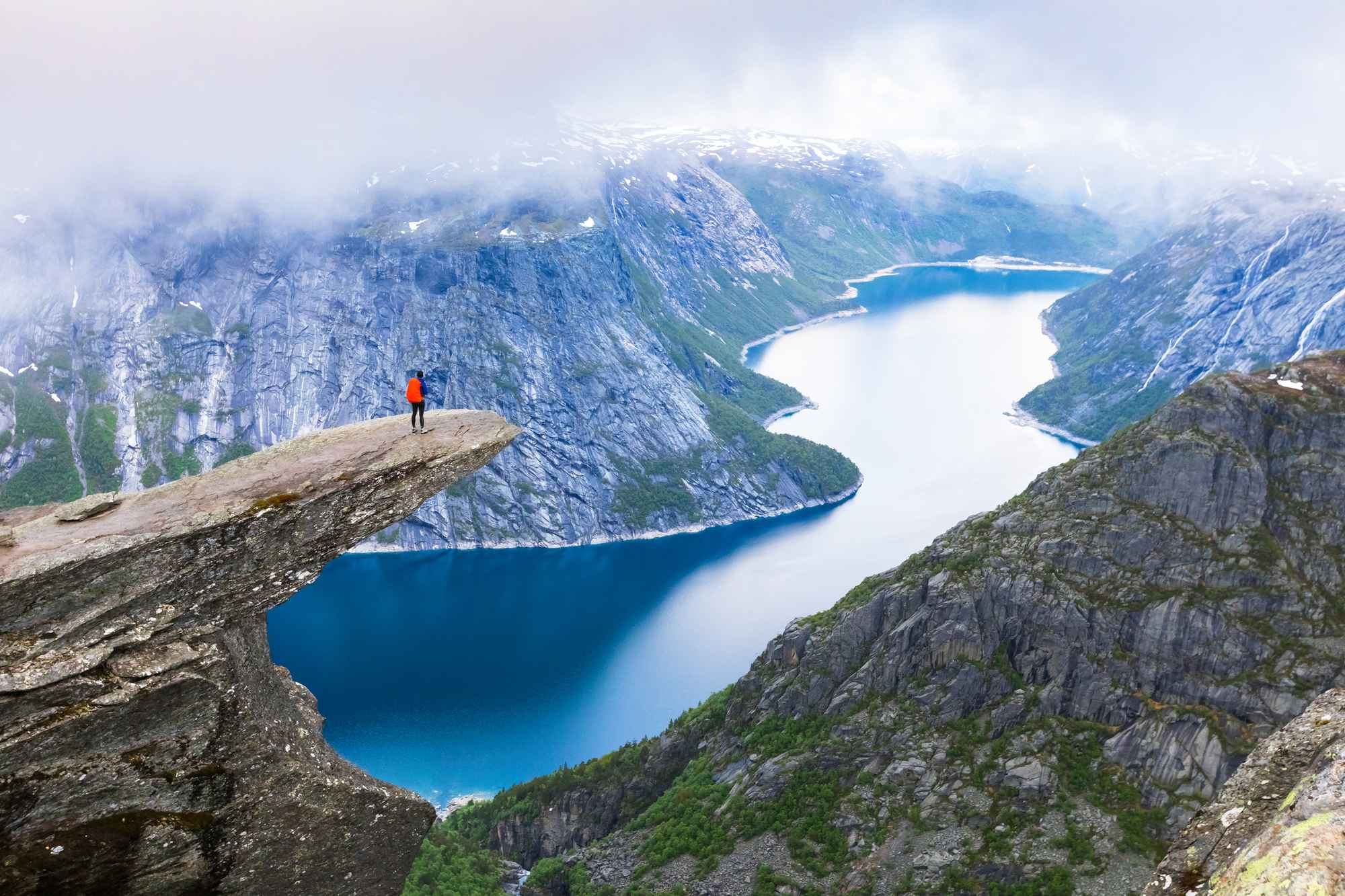 Hiker-standing-on-Trolltunga-with-panoramic-view-of-lake,-Norway-804595788_2125x1417