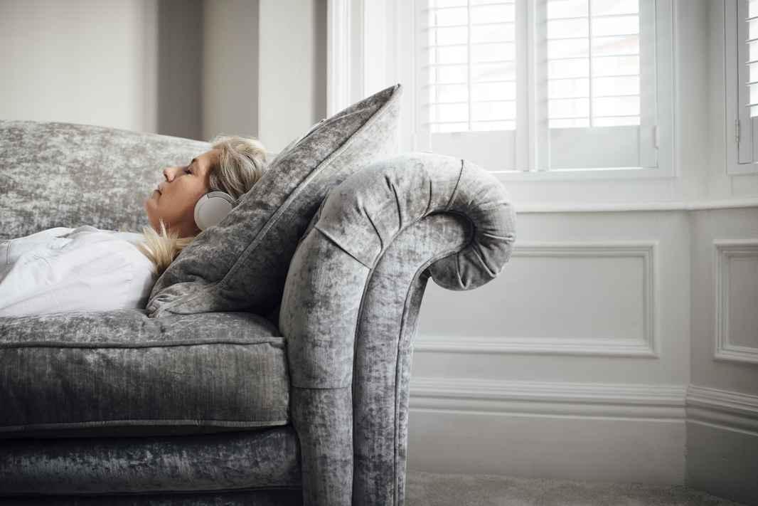Kvinde - ligger i sofa med hovedtelefoner - mediterer