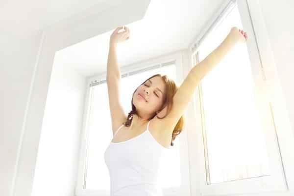 woman-waking-up-stretching-window_axco9u