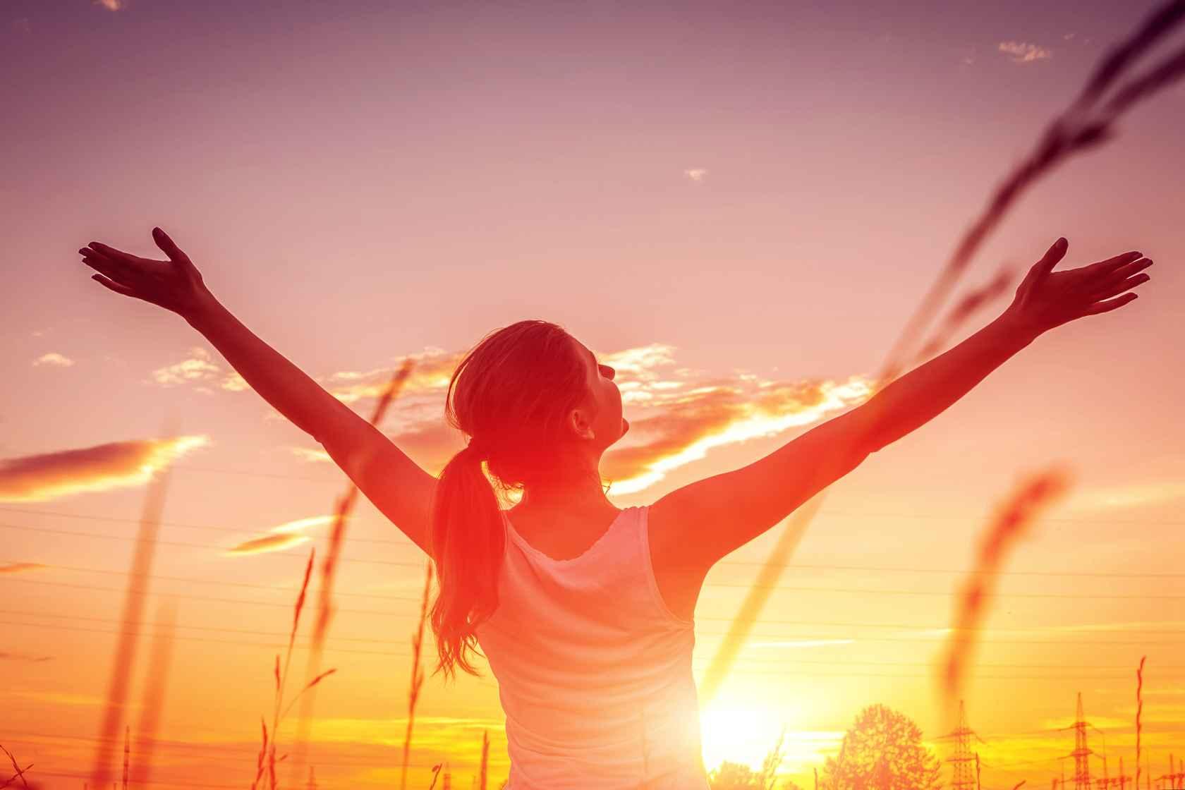 kvinde løfter arme mod solnedgangen.jpg