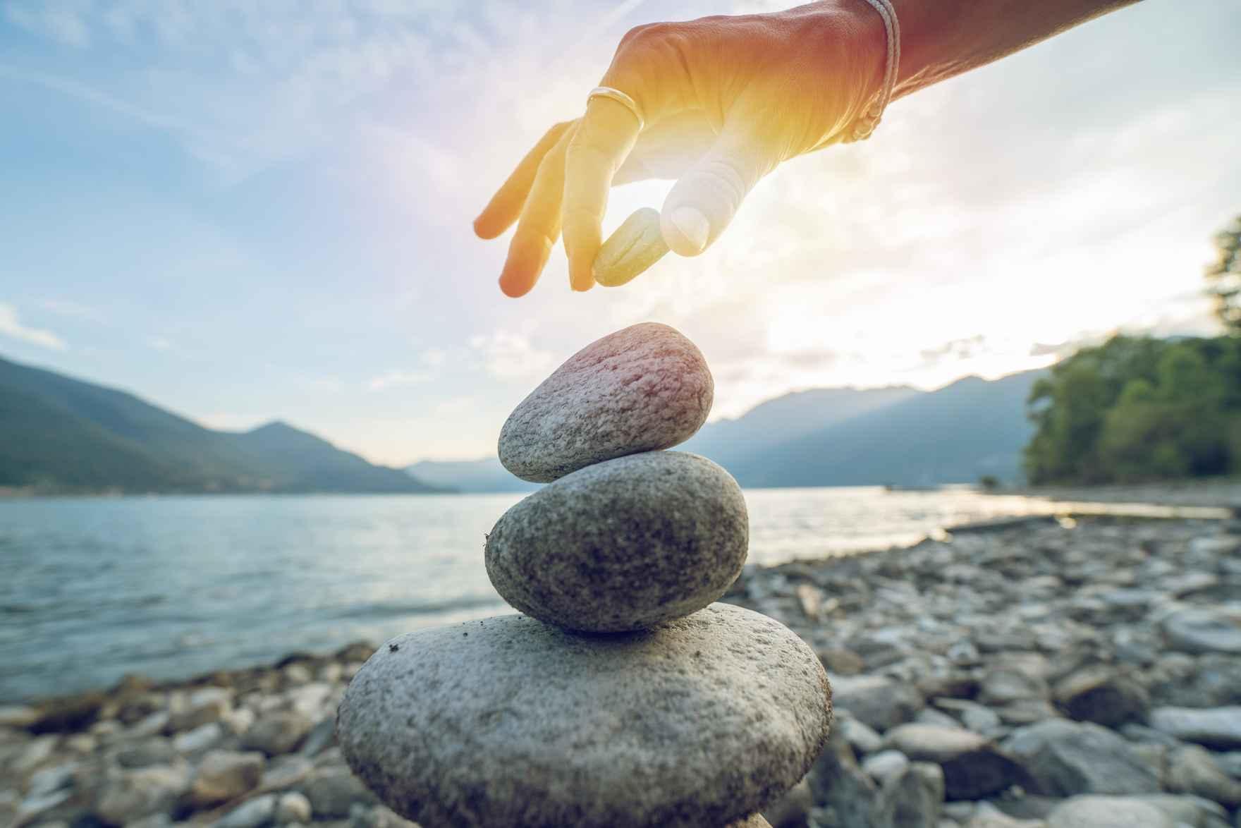 Hånd lægger sten på stenbunke ved sø