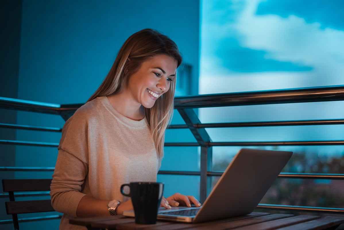 Kvinde ved computer på balkon smiler .jpg