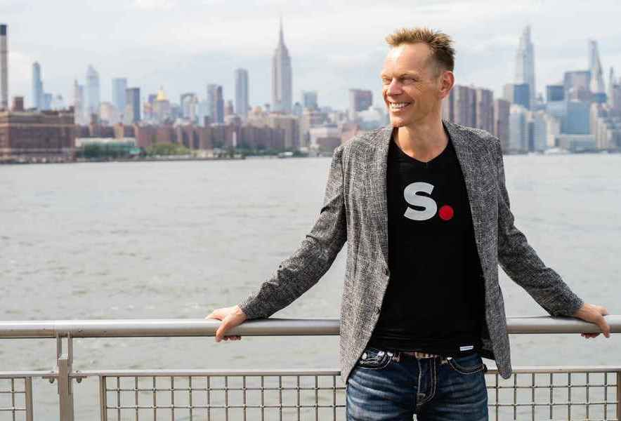 Calvin smiling and looking away from the camera wearing a jeans, black Simplero t-shirt and a gray blazer leaning against a railing in front of a lake with a city skyline behind him