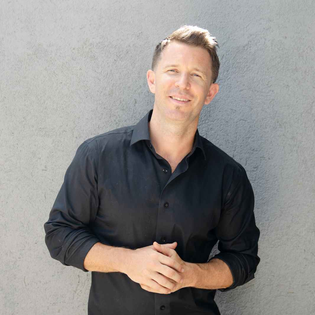 Damon smiling, wearing a black shirt with arms clasped in front of his chest against a gray concrete wall
