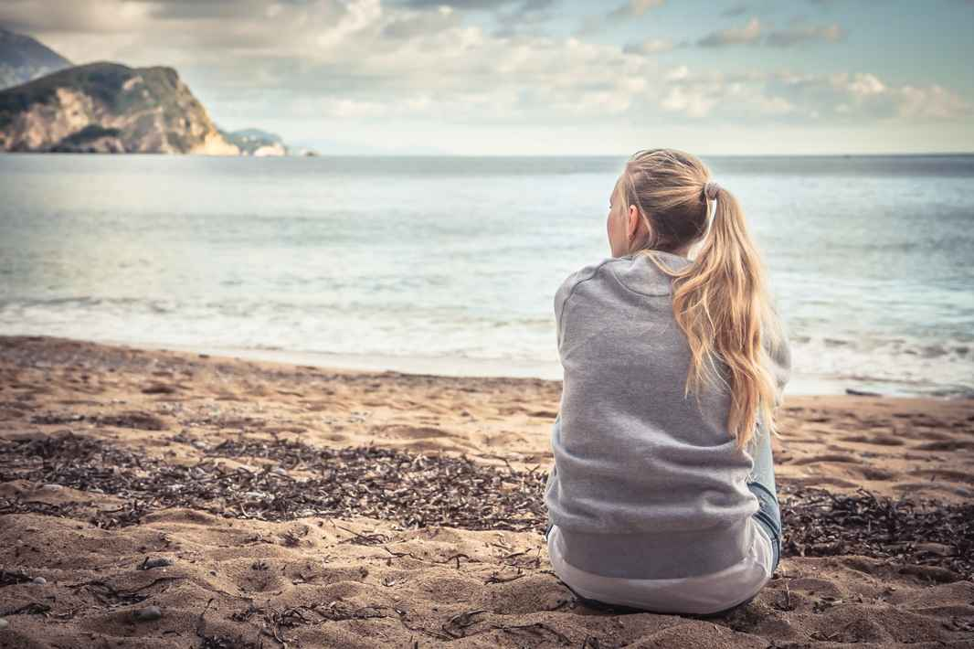 Kvinde sidder eftertænksomt på stranden