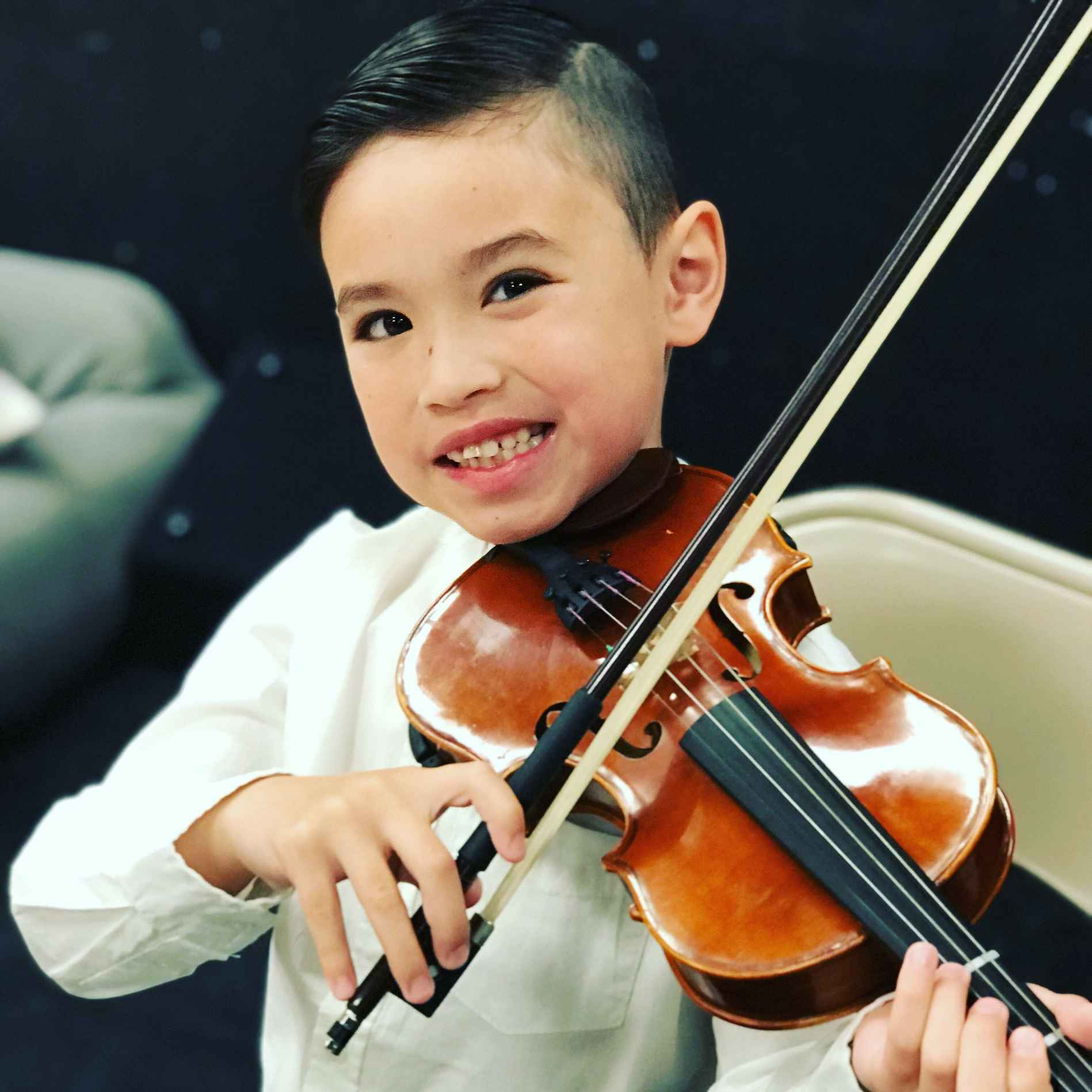 smiling boy playing violin
