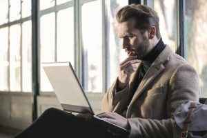 Canva-Man-Wearing-Brown-Jacket-and-Using-Grey-Laptop-300x200