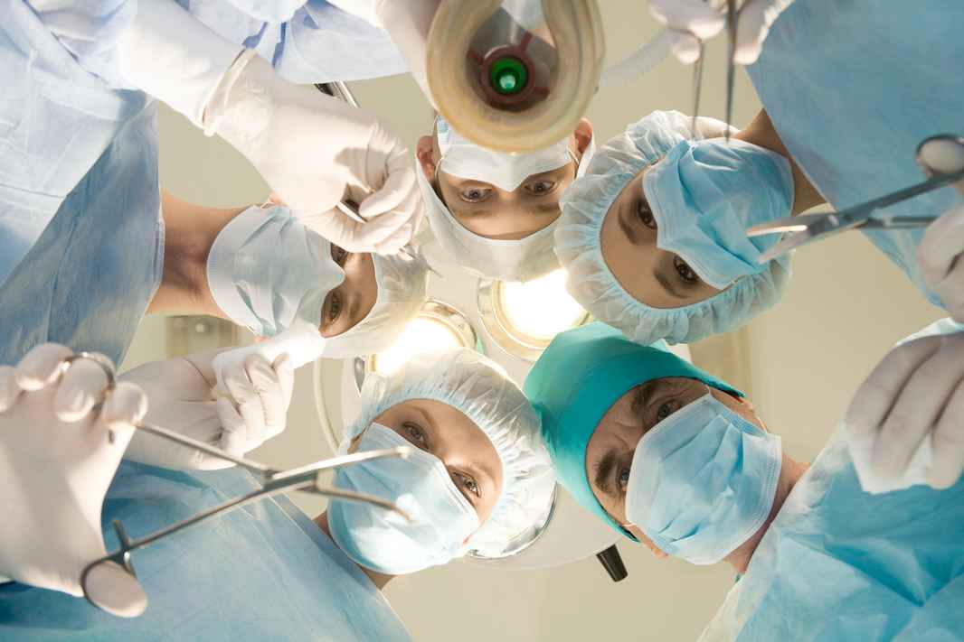 below-view-of-surgeons-holding-medical-instruments-in-hands-and-looking-at-patient