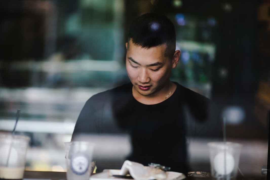 storyblocks-window-view-of-an-asian-man-in-an-office_BnZt4IxhKD