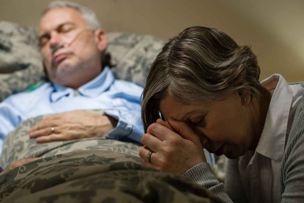 senior-woman-praying-for-sick-man-sleeping-in-hospital-bed