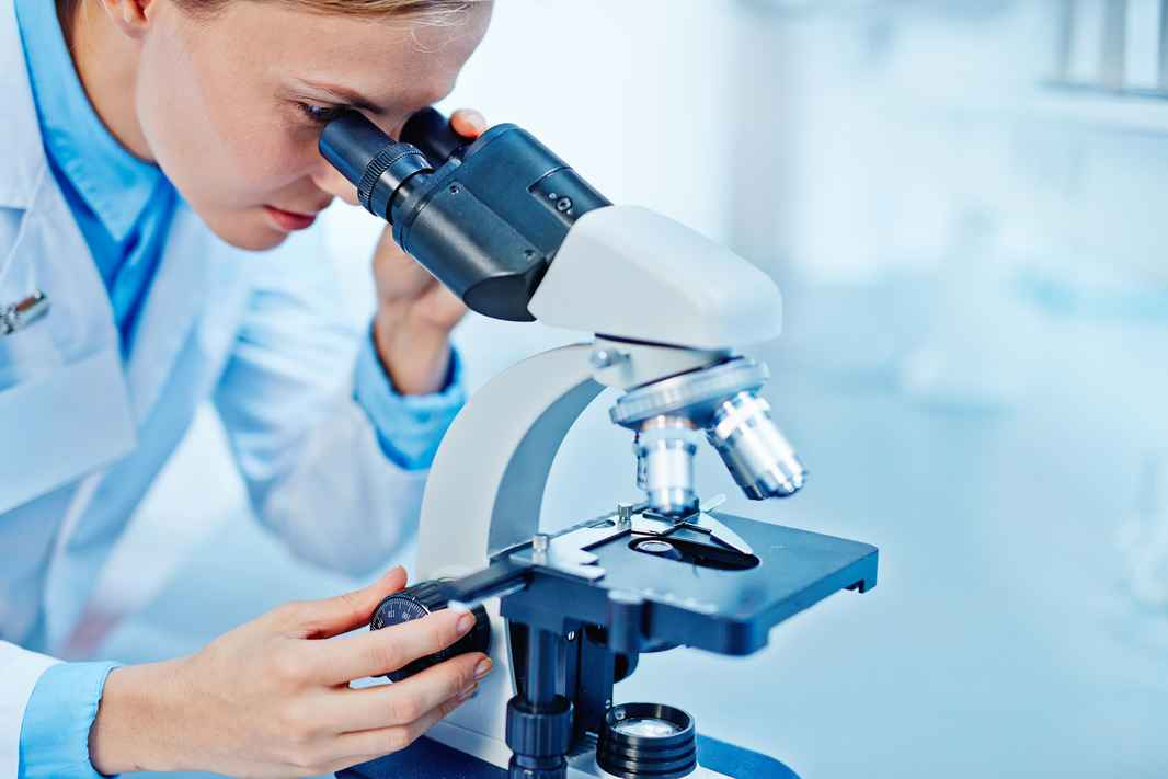 graphicstock-young-female-chemist-looking-in-microscope-in-lab_H7wX6PIMVW
