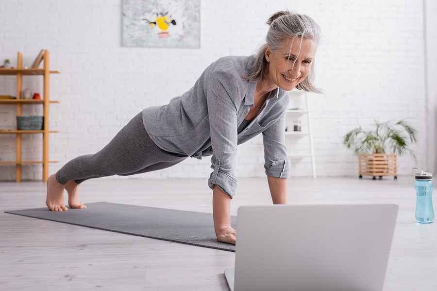 mature woman practicing yoga at home